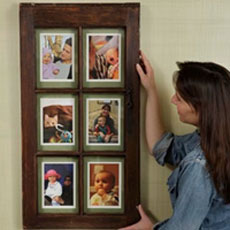 woman hangs picture frame on wall