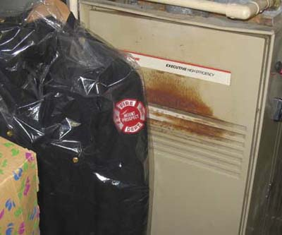 fire uniform hung in front of a furnace causing a fire hazard
