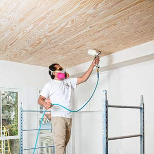 spraying clear finish over whitewashed pine ceiling in the TOH TV Cambridge house