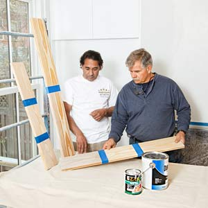 painter Mauro Henrique shows Tom Silva samples of whitewashed wood for ceiling in the TOH TV Cambridge house