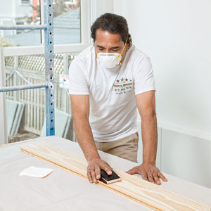 painter Mauro Henrique preps pine for whitewashing in the TOH TV Cambridge house