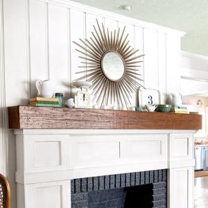 fireplace redo after with white wood trim, rustic mantelshelf and black-painted firebox