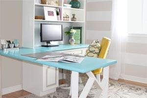 light blue l-shaped desk built into a white bookshelf to the left of a bright window in a wall with horizontal beige stripes