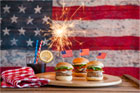 three sliders with small paper american flag toothpics sticking out of the top on a wood plate next to a small glass with a dark liquid, a lemon slice and red-white-and-blue straws, all set in front of an american flag