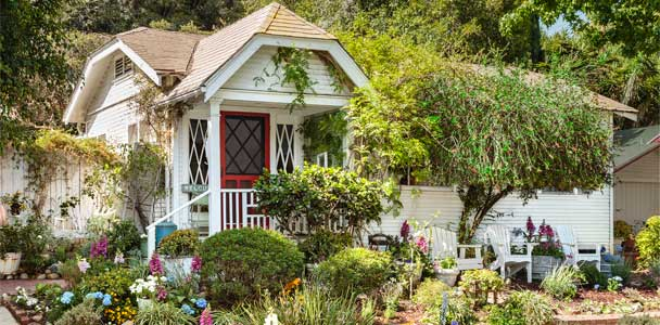 remodeled 1920s country cottage house set back on a hill with terraced gardens leading up to the front porch