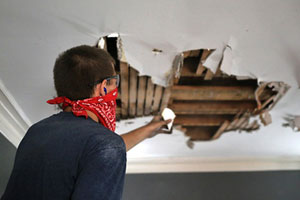 person wearing safety glasses and a handkerchief tied over their nose and mouth, reaching up toward the lathe and joists exposed by a hole in the plaster ceiling
