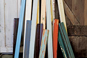 stacks of salvaged molding in different sizes, styles, and colors collected and leaned against a wall of other salvaged woods