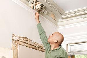 Scott Omelianuk inspecting some plaster ceiling ornamentation