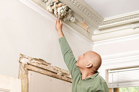 Scott Omelianuk inspecting some plaster ceiling ornamentation