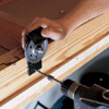 Install cable pulleys to enable pulley system to slide stairs down when attic door is opened