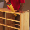 using a handsaw to trim the ends off of a dresser