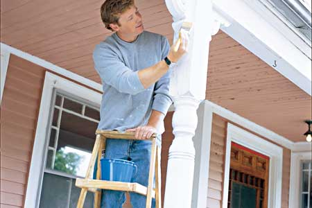 Toh host Kevin O'Conner on a step ladder painting the porch