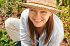 woman wearing wide brimmed hat while working in garden to protect skin from sun