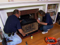 richard and a fireplace expert help a homeowner install a new gas fireplace insert