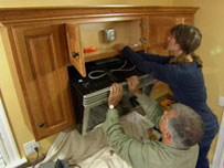 tom silva helps a homeowner install a combination range hood and microwave oven over her kitchen stovetop
