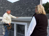 tom and a homeowner check the newly installed house gutters