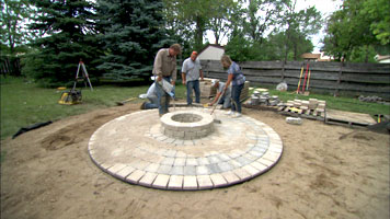 roger helping a homeowner build and circular patio and fire pit