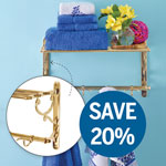 brass railway shelf installed on a blue wall, with deeper blue and white towels folded and stacked on the shelf, and a small glass vase with flowers sitting next to the towels. An inset shows the side decoration of the shelf
