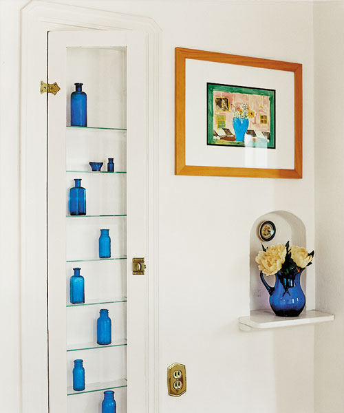display case made by retrofitting a built-in ironing-board cubby with a glass door panel and shelves