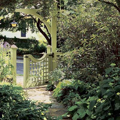 Garden with an arch entry and paved walkway has a hanging lampost