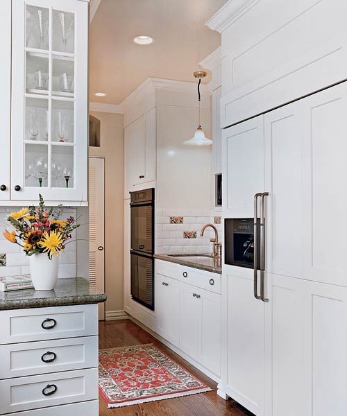 Refrigerator, wall ovens, secondary sink and a pantry serves as a prep-and-cleanup zone.