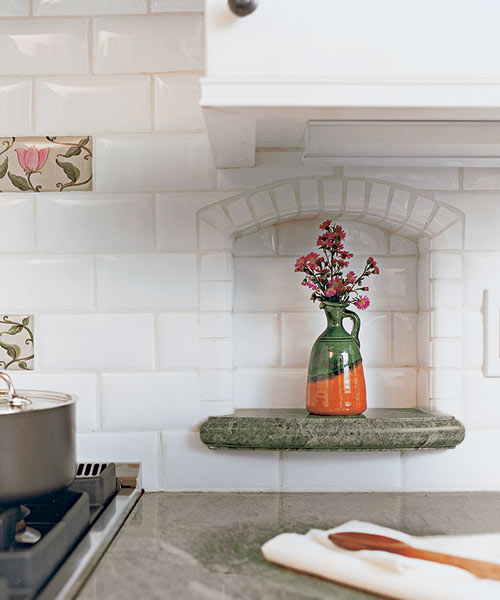 Sage-green granite countertop with arched tiled niches holds an accent piece