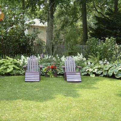 backyard of garden transformed, with Adirondack chairs