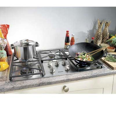 Miele stove top with a pot and wok