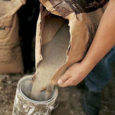 man pouring sand from a bag into a barrel