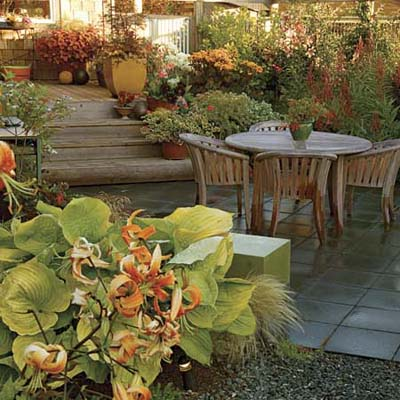 concrete paver patio with wood patio furniture, surrounded by colorful plants with rich green foliage; wood deck attached to shingled house