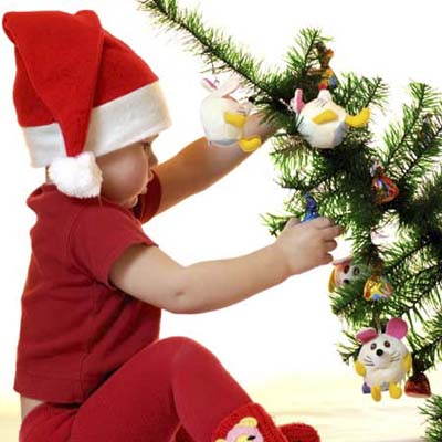 child pulling down a fully decorated christmas tree
