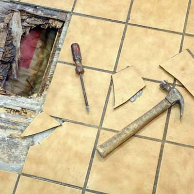 a hole in the floor with floor tiles in a state of repair