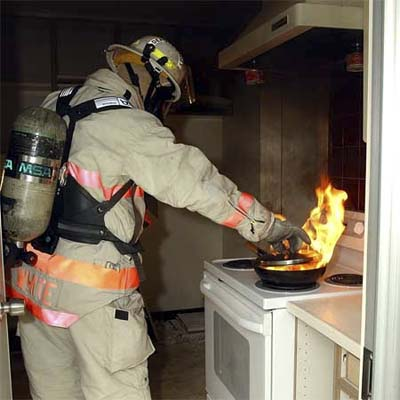 fireman putting out a flaming fry pan in a kitchen