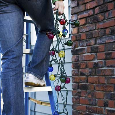 person standing on ladder in front of a house with string of holiday lights in one hand