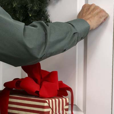one hand knocking on decorated front door of a house while the other holds a wrapped gift