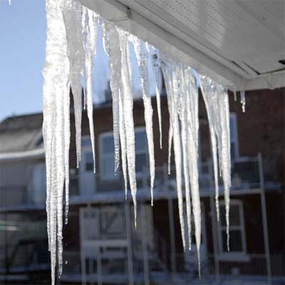 large icicles hanging under the eves of a house