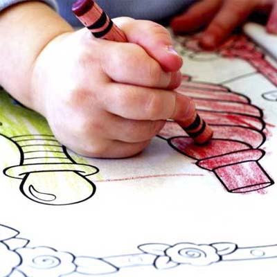 child's hand coloring with crayon