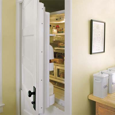 salvaged door used as a front to a built in refrigerator to hide the unit while fitting seamlessly to the vintage look of this modern kitchen