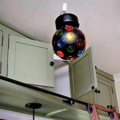 a strobe light hidden in an upper cabinet swings out so this vintage look kitchen can turn into a dance floor for entertaining guests