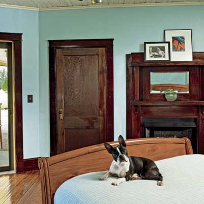 boston bulldog lying on bed in bungalow's master bedroom after renovation with vent-free gas fireplace