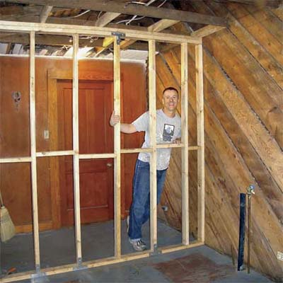 bungalow homeowner standing behind bare studs in unfinished room