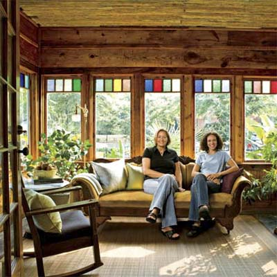 homeowners sitting in brightly lit reader remodeled sunroom