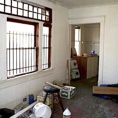 living area during the remodel with bars on the windows and construction materials everywhere