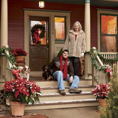 mother and son sitting on front porch of remodel decorated for the holidays