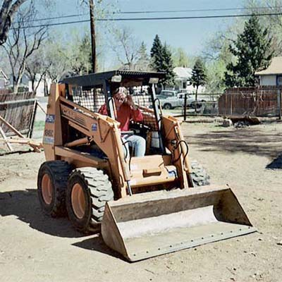 homeowner driving her rented skid-steer in the yard during her remodel