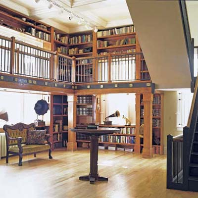 two-story library with pedestal table and tall ceiling in former post office