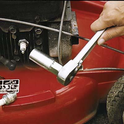 hand repairing lawn mower