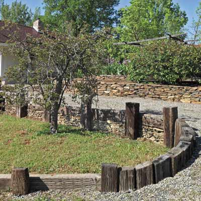 a retaining wall that is also edging for a gravel driveway