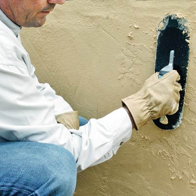 man applying stucco to a retaining wall