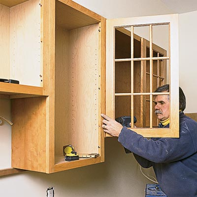 t o h contractor tom silva installing a kitchen cabinet